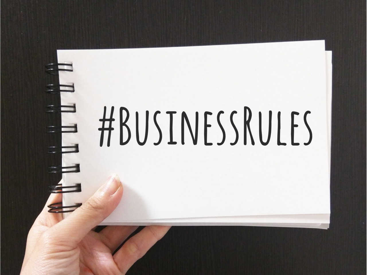 a hand holding a notebook that says Business Rules